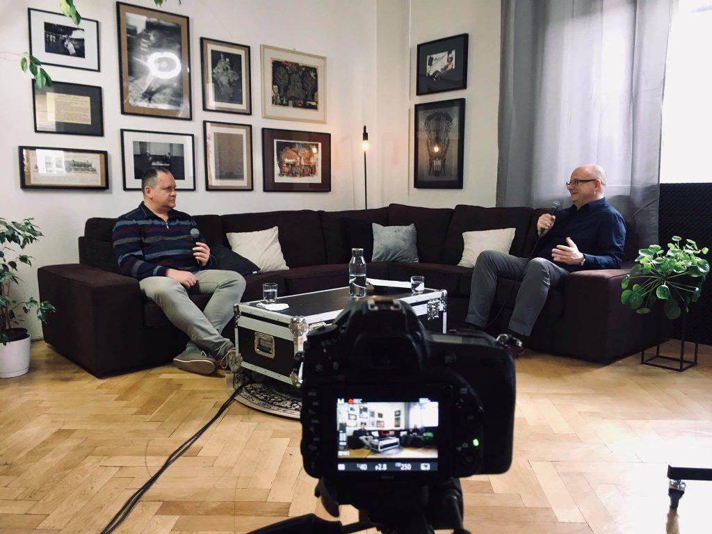Branislav Moťovský a Ivan Ježík sediaci na gauči počas rozhovoru, v popredí displej fotoaparátu