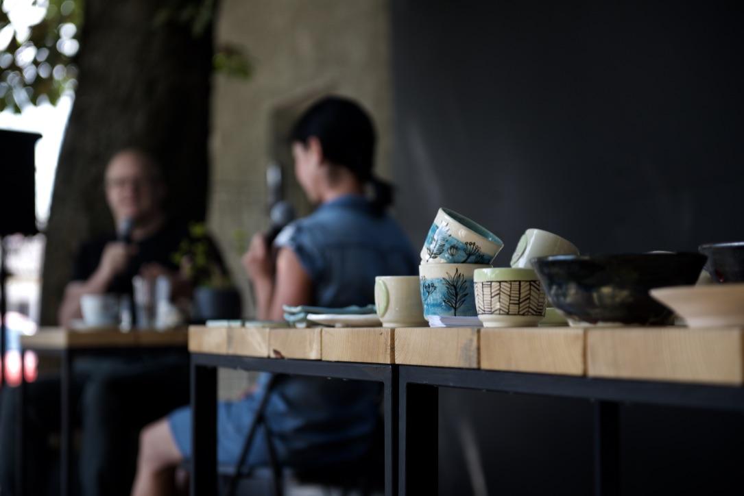 v popredí keramické šálky na stole, v pozadí moderátor s hosťkou pri rozhovore